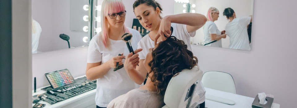 Portrait of make-up artist teaching to make good makeup in a beauty center
